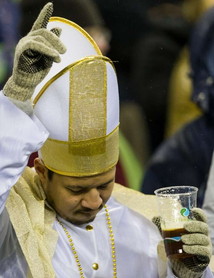 A Saints fan enjoys an adult libation during the first half of game Monday, Dec. 2, 2013, at CenturyLink Field in Seattle. The Seahawks led the Saints 27-7 at the end of the first half. Photo: JORDAN STEAD, SEATTLEPI.COM