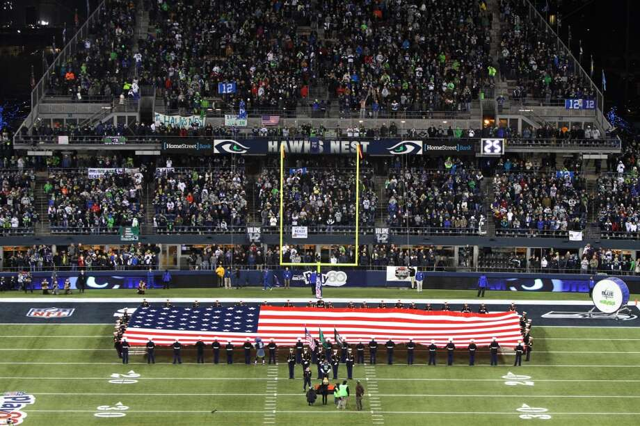 The American flag is unfolded on the field before the start of the Seahawks and Saints game Monday, Dec. 2, 2013, at CenturyLink Field in Seattle. Photo: MARK MALIJAN, SEATTLEPI.COM
