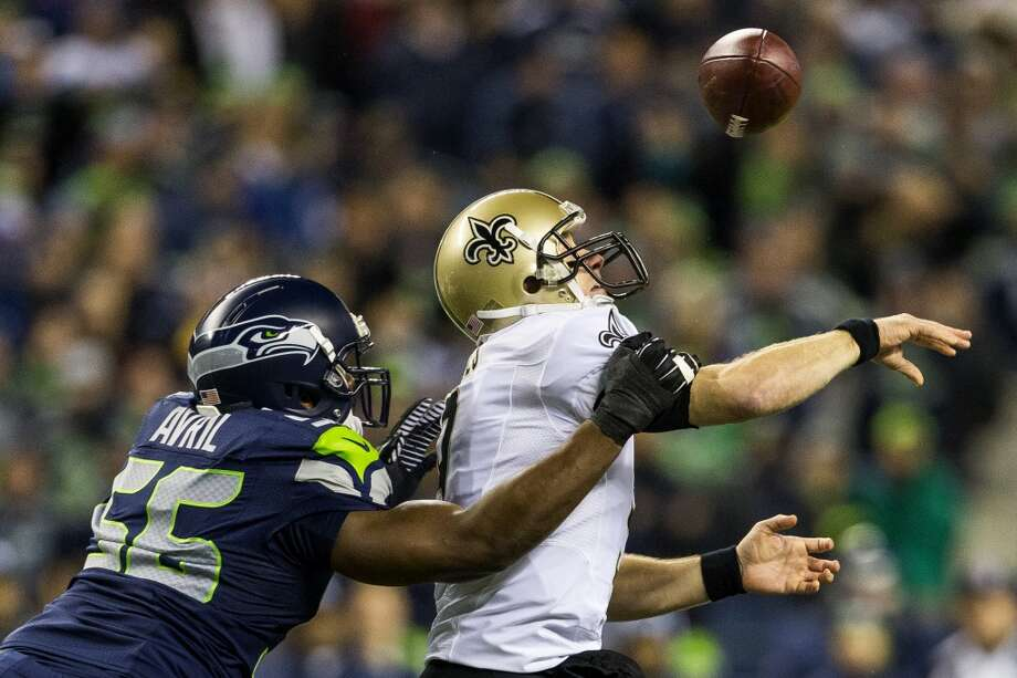 Seahawk Cliff Avril, left, knocks the ball free from the hand of the New Orleans Saints' quarterback, Drew Brees, right, during the first half of game Monday, Dec. 2, 2013, at CenturyLink Field in Seattle. The Seahawks led the Saints 27-7 at the end of the first half. Photo: JORDAN STEAD, SEATTLEPI.COM