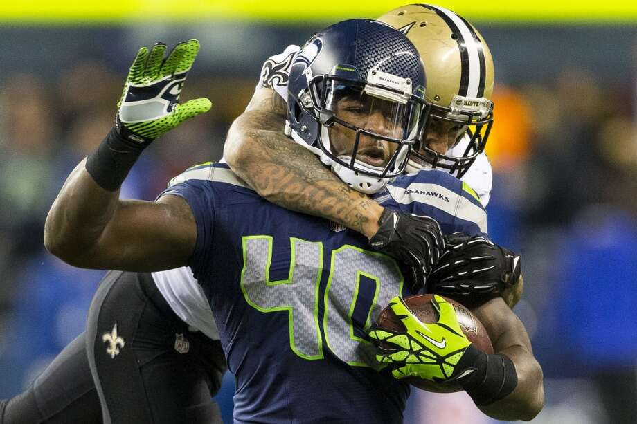 Seahawk Derrick Coleman, foreground, is tackled by a New Orleans Saints' player during the second half of game Monday, Dec. 2, 2013, at CenturyLink Field in Seattle. The Seahawks beat the Saints 34-7. Photo: JORDAN STEAD, SEATTLEPI.COM