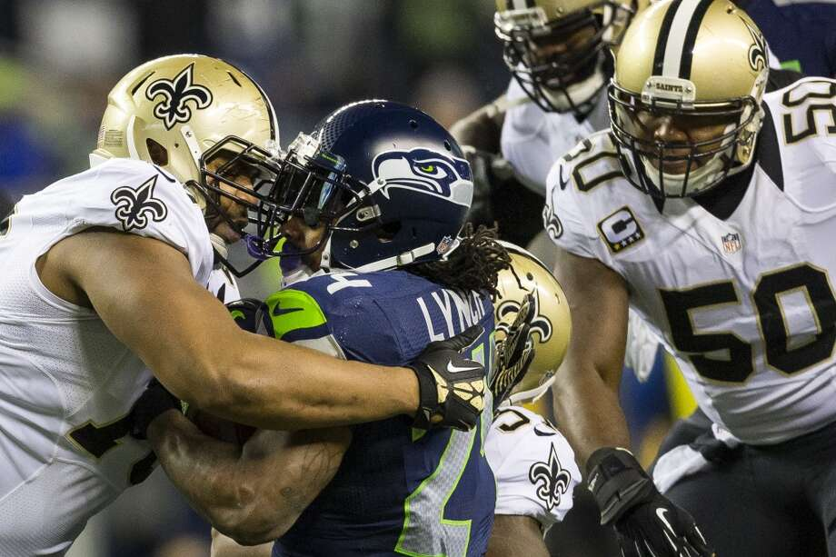 Marshawn Lynch, center left, is taken down by the New Orleans Saints during the first half of game Monday, Dec. 2, 2013, at CenturyLink Field in Seattle. The Seahawks led the Saints 27-7 at the end of the first half. Photo: JORDAN STEAD, SEATTLEPI.COM