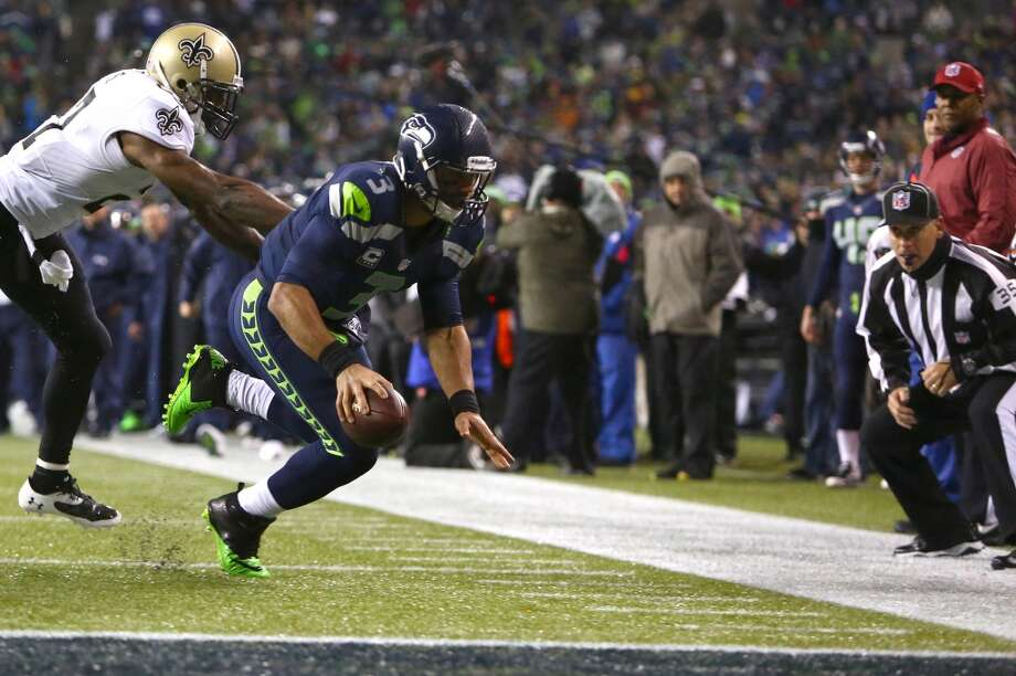 Seahawks quarterback Russell Wilson tries for a touchdown while defended by Saints player Malcolm Jenkins during an NFL game on Monday, Dec. 2, 2013, at CenturyLink Field in Seattle. Photo: JOSHUA TRUJILLO, SEATTLEPI.COM