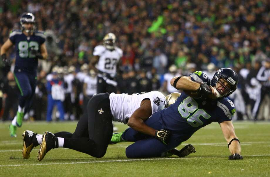 Seahawks player Zach Miller is taken down by a Saints player after gaining yardage during an NFL game on Monday, Dec. 2, 2013, at CenturyLink Field in Seattle. Photo: JOSHUA TRUJILLO, SEATTLEPI.COM