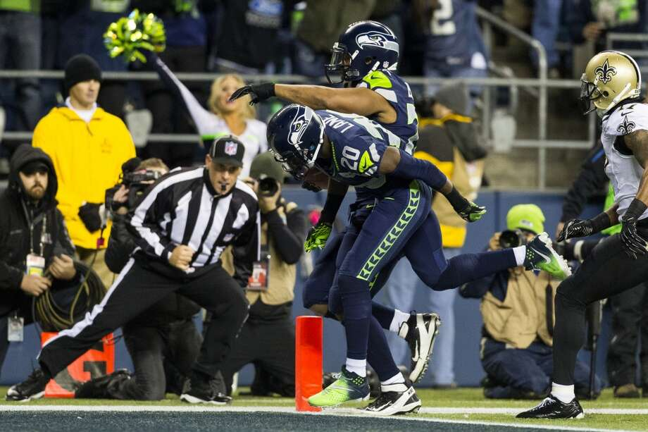 Seahawk Michael Bennett, background, runs in a touchdown off of a fumble return during the first half of game against the New Orleans Saints Monday, Dec. 2, 2013, at CenturyLink Field in Seattle. The Seahawks led the Saints 27-7 at the end of the first half. Photo: JORDAN STEAD, SEATTLEPI.COM