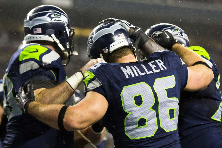 Seahawk Zach Miller, center, celebrates with teammates after scoring a touchdown against the Saints during the first half of game Monday, Dec. 2, 2013, at CenturyLink Field in Seattle. The Seahawks led the Saints 27-7 at the end of the first half. Photo: JORDAN STEAD, SEATTLEPI.COM