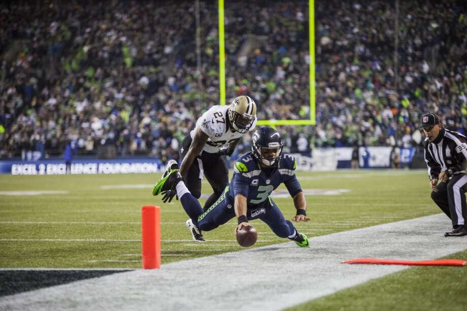 Saints Malcolm Jenkins pushes Seahawks Russell Wilson out of bounds in the second quarter on Monday, Dec. 2, 2013, at CenturyLink Field in Seattle. Photo: MARK MALIJAN, SEATTLEPI.COM