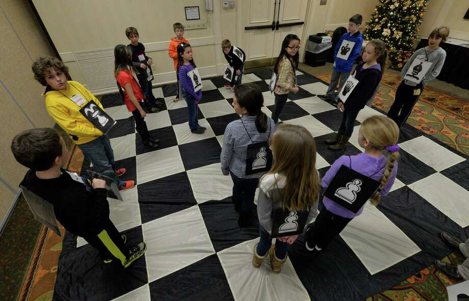 Fourth and fifth graders from six elementary schools in the city of Saratoga enjoy a game of human chess during Young Mathematicians Day Monday morning, Dec. 2, 2013, at the Holiday Inn in Saratoga Springs, N.Y. Using a chess board the students will learn angles and logic as part of their math day program. (Skip Dickstein/Times Union) Photo: SKIP DICKSTEIN / 00024848A