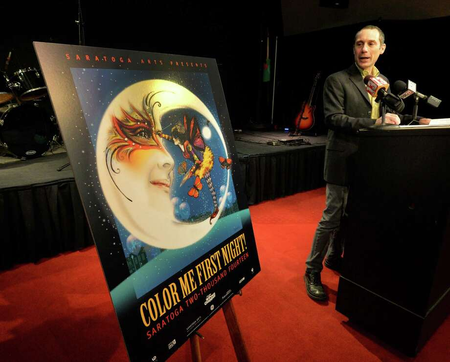 Joel Reed, executive director for the Saratoga Arts, unveils this year's First Night poster by artist Sharon Bolton Monday morning, Dec. 2, 2013, during a press conference in Saratoga Springs, N.Y. (Skip Dickstein/Times Union) Photo: SKIP DICKSTEIN / 00024715A