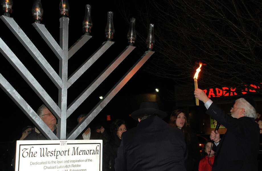 A large menorah was lighted at a community Hanukkah celebration organized Monday by the  Schneerson Center for Jewish Life at Compo Acres shopping center. Photo: Jarret Liotta / Westport News contributed