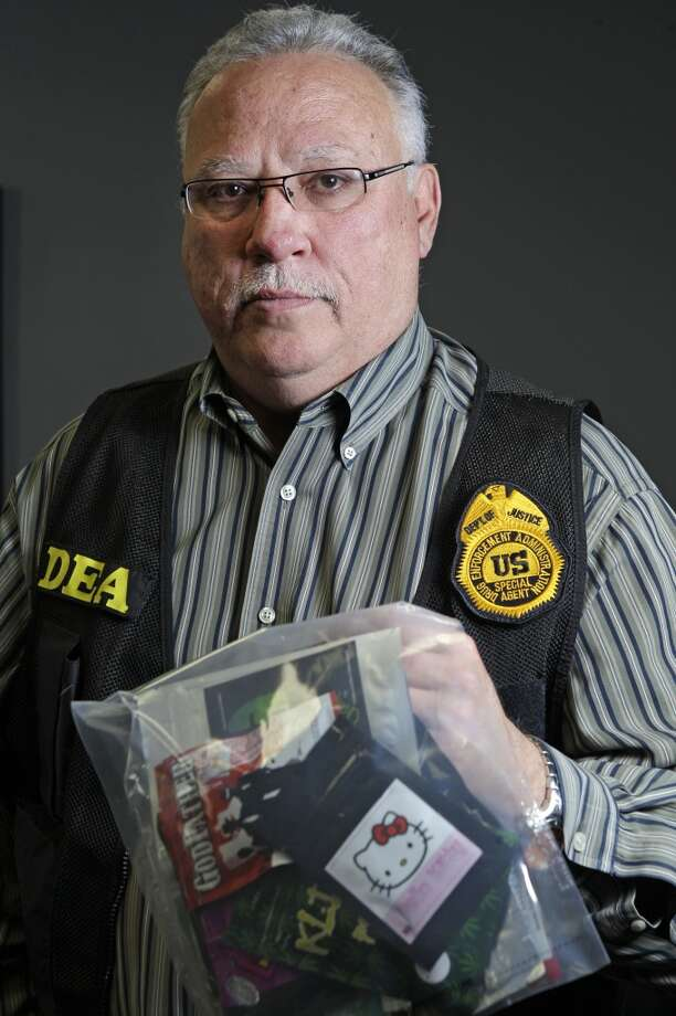 Javier Pena, head of the Drug Enforcement Administration's Houston Division, holds packages of so-called synthetic marijuana. (Melissa Phillip/ Houston Chronicle)