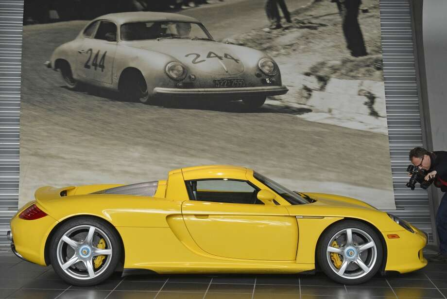 A photographer shoots photos of a Porsche Carrera GT in the historical exhibition at the plant of the sport car manufacturer Porsche AG in Leipzig, central Germany, Wednesday, March 28, 2012. Photo: Jens Meyer, AP