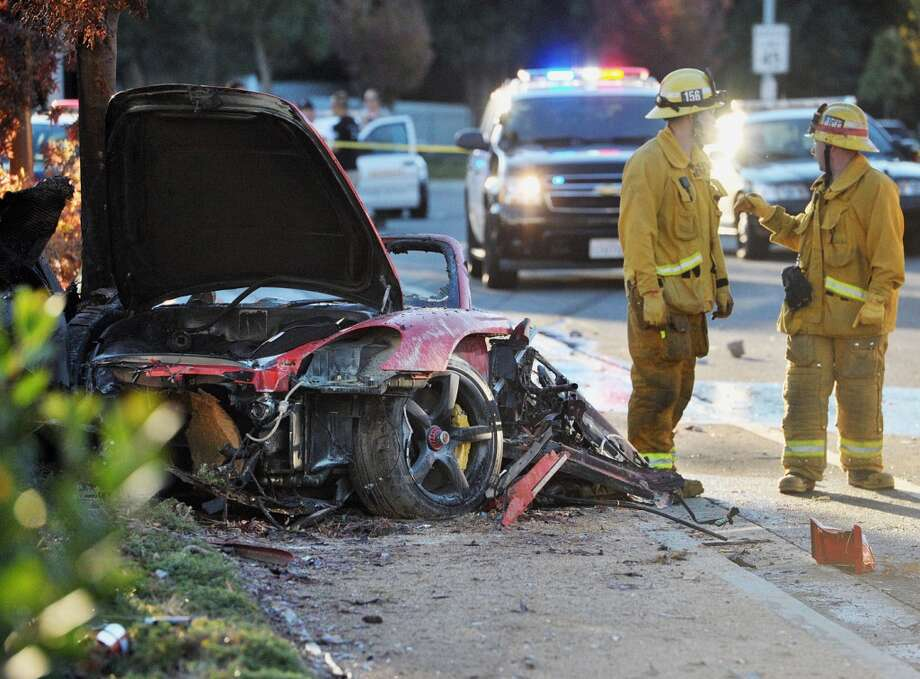 First responders gather evidence near the wreckage of a Porsche Carrera GT that crashed into a light pole on Hercules Street near Kelly Johnson Parkway in Valencia on Saturday, Nov. 30, 2013. Photo: Dan Watson, ASSOCIATED PRESS