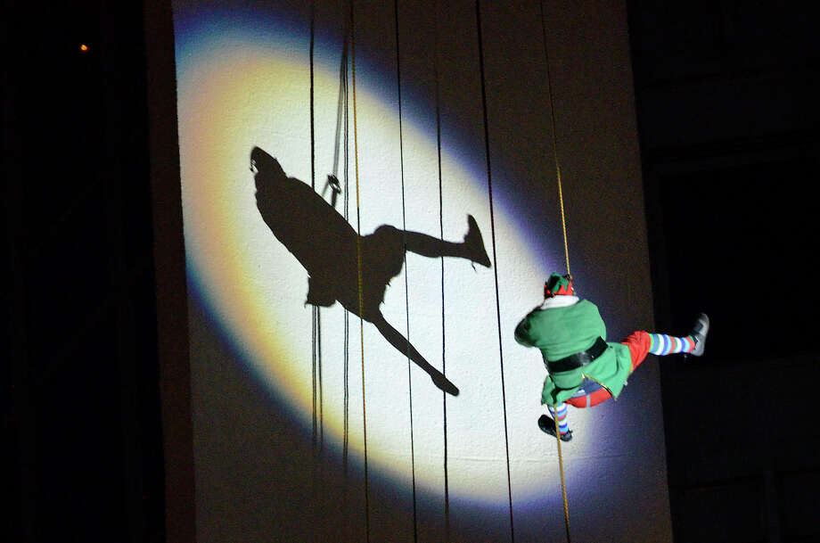 One of Santa's elves rappels off the Landmark building in downtown Stamford, Conn., on Sun., Dec. 4, 2011, as part of the Heights & Lights celebration hosted by the Stamford Downtown Special Services District. It returns on Sunday, Dec. 8, 2013, featuring special guests, Santa and a tree-lighting ceremony. Visit  http://stamford-downtown.com. Photo: Shelley Cryan / Shelley Cryan freelance; Stamford Advocate freelance