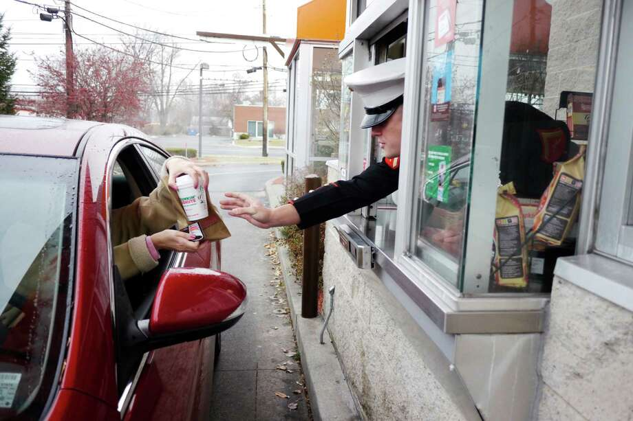 US Marine Lance Corporal, Joe Iachetta from Waterford, hands an order to a customer at the Dunkin' Donuts on Central Ave. on Tuesday, Dec. 3, 2013 in Albany, NY.  Iachetta handed out orders at the drive thru and the counter, telling customers about the Marine's Toys of Tots program and also telling them that their order was free, being covered by Dunkin' Donuts.  Many of the customers then donated money above the cost of their order to the toy program.  The Marine Corps Reserves' Dunkin' Donuts Toys for Tots Train will run this Saturday and Sunday, Dec. 7th and 8th.  Dunkin' Donuts locations in the area are still collecting toys for the program.  The popular doughnut shop has donated $30,000 to the toy program this year and over $140,000 in the past 5 years.  (Paul Buckowski / Times Union) Photo: PAUL BUCKOWSKI / 00024859A