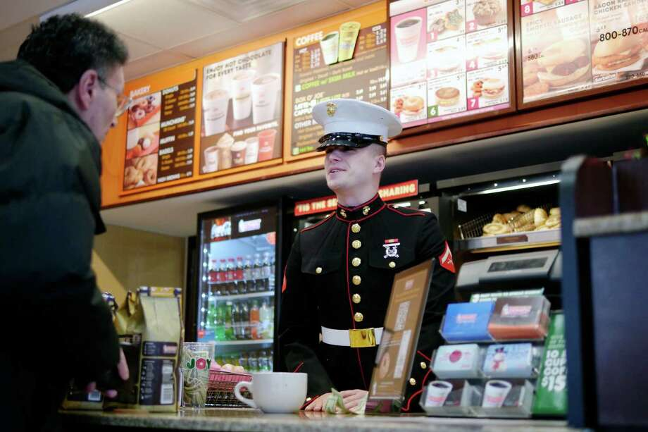US Marine Lance Corporal, Joe Iachetta from Waterford, tells a customer his order is free at the Dunkin' Donuts on Central Ave. on Tuesday, Dec. 3, 2013 in Albany, NY.  Iachetta handed out orders at the drive thru and the counter, telling customers about the Marine's Toys of Tots program and also telling them that their order was free, being covered by Dunkin' Donuts.  Many of the customers then donated money above the cost of their order to the toy program.  The Marine Corps Reserves' Dunkin' Donuts Toys for Tots Train will run this Saturday and Sunday, Dec. 7th and 8th.  Dunkin' Donuts locations in the area are still collecting toys for the program.  The popular doughnut shop has donated $30,000 to the toy program this year and over $140,000 in the past 5 years.  (Paul Buckowski / Times Union) Photo: PAUL BUCKOWSKI / 00024859A