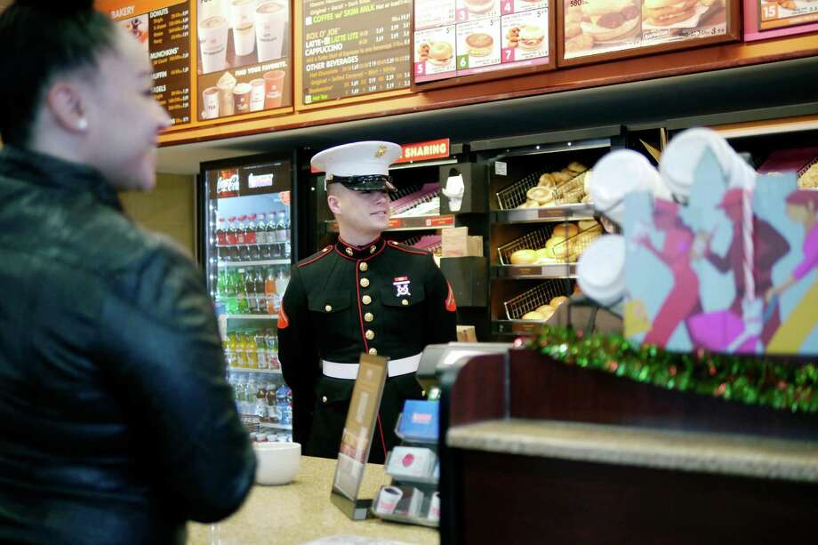 US Marine Lance Corporal, Joe Iachetta from Waterford, works behind the counter at the Dunkina€™ Donuts on Central Ave. on Tuesday, Dec. 3, 2013 in Albany, NY.  Iachetta handed out orders at the drive thru and the counter, telling customers about the Marine's Toys of Tots program and also telling them that their order was free, being covered by Dunkina€™ Donuts.  Many of the customers then donated money above the cost of their order to the toy program.  The Marine Corps Reserves' Dunkin' Donuts Toys for Tots Train will run this Saturday and Sunday, Dec. 7th and 8th.  Dunkina€™ Donuts locations in the area are still collecting toys for the program.  Dunkina€™ Donuts has donated $30,000 to the toy program this year and over $140,000 in the past 5 years.   (Paul Buckowski / Times Union) Photo: PAUL BUCKOWSKI / 00024859A