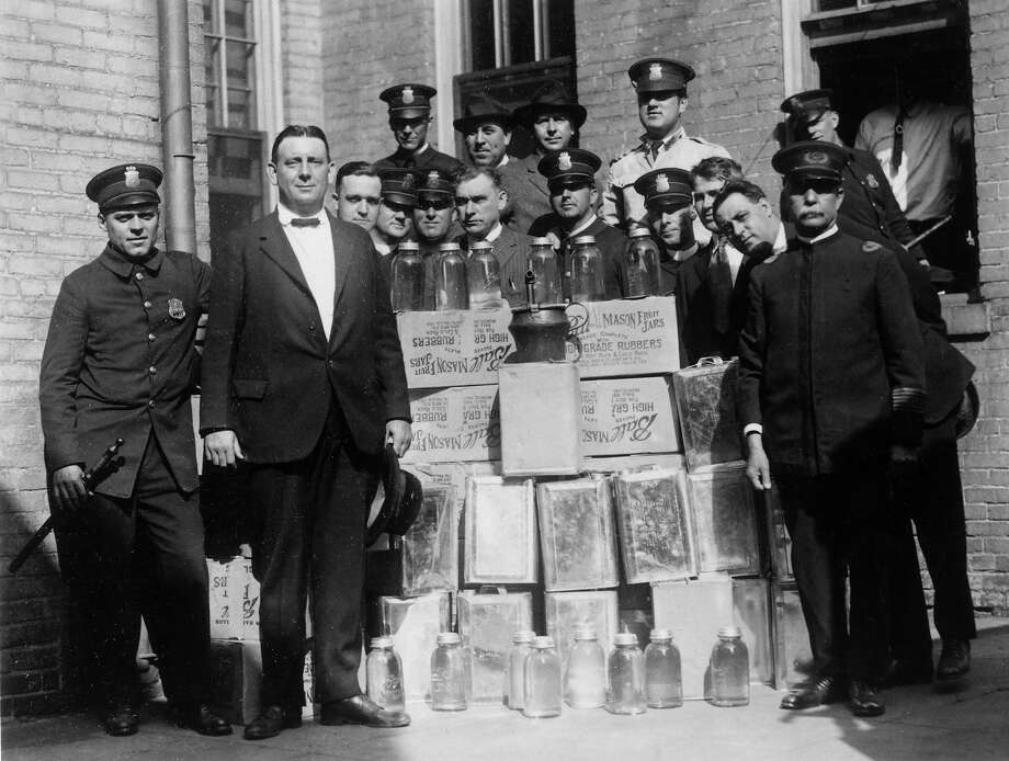 Group portrait of a police department liquor squad posing outdoors with cases of confiscated alcohol and distilling equipment during prohibition. Photo: Archive Photos, Getty Images / Archive Photos