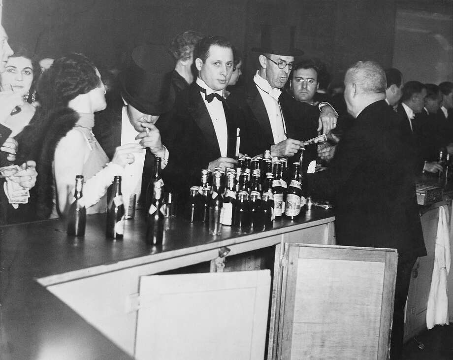 Evening dressed revelers buying their drinks at a bar at the time of prohibition. Photo: Keystone, Getty Images / Hulton Archive