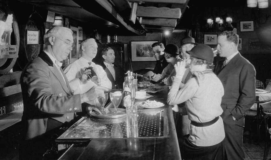 During the dark days: Patrons enjoying drinks at the Hunt Club. a speakeasy with a filing system listing their 23,000 eligible customers which is checked before a customer gets through the door at this venue that is protected from police prohibition raids. Photo: Margaret Bourke-White, Time & Life Pictures/Getty Image / Margaret Bourke-White