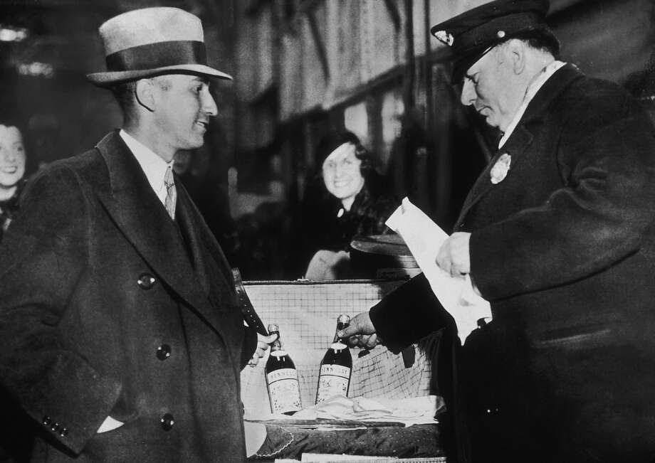 Arthur Ernstahl, the first person to bring liquor into the U.S legally after the repeal of The Eighteenth Amendment, declares two bottles of cognac to customs inspector Leo Shettel after arriving in New York on the Monarch of Bermuda, 5th December 1933. Photo: New York Times Co., Getty Images / 2007 Getty Images