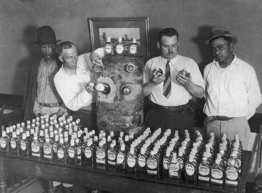 California prohibition agents with a vehicle fuel tank and the 250 bottles of tequila, which were hidden in it and smuggled into the US from Mexico, circa 1930. On the left and right are the two men, who were arrested with the contraband. Photo: FPG, Getty Images / 2008 Getty Images