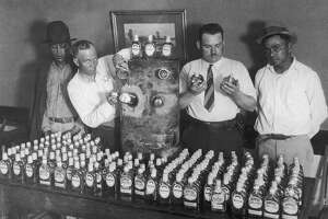 California prohibition agents with a vehicle fuel tank and the 250 bottles of tequila, which were hidden in it and smuggled into the US from Mexico, circa 1930. On the left and right are the two men, who were arrested with the contraband.