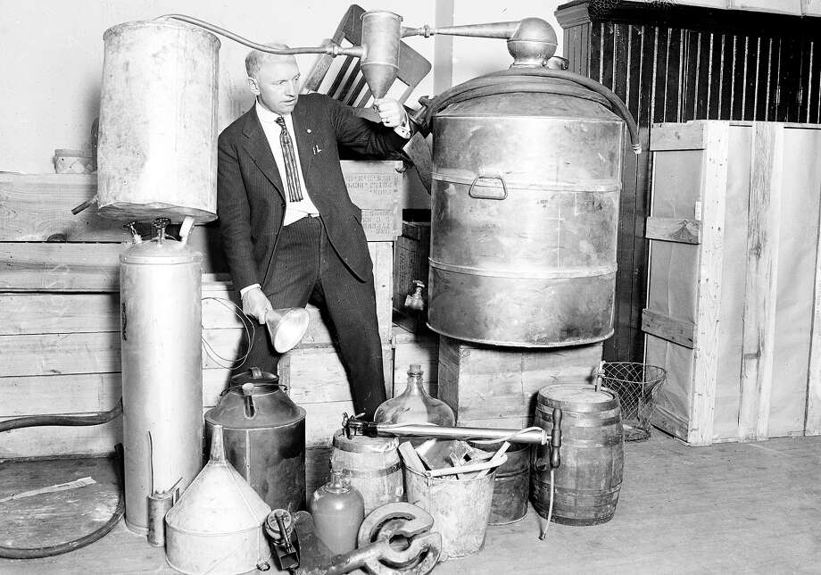 Edwin C. Arthur stands in the center of a collection of containers of moonshine taken during a South Side raid in Chicago, Illinois, 1922 Photo: Chicago History Museum, Getty Images / Property of Chicago Historical Society.  Not to be reproduced or used without written permission from CHS Rights & Reproductions Dept.