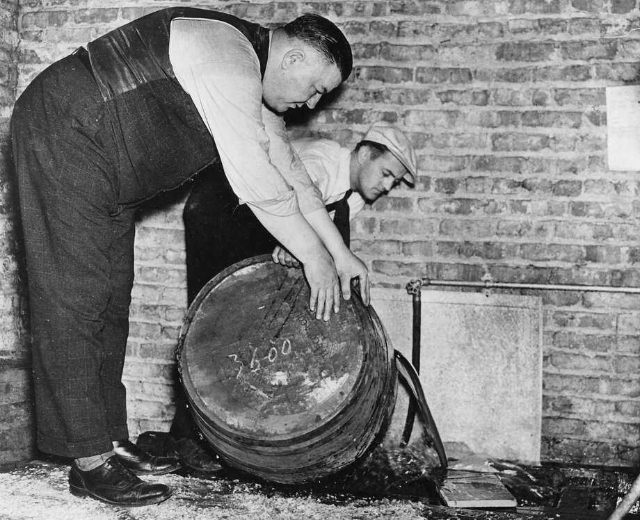 Two men pour out the contents of barrels of confiscated moonshine, Chicago, ca.1920s. Home-distilled moonshine was fermented in wooden barrels to make it taste more like whiskey. Photo: Chicago History Museum, Getty Images / Property of Chicago Historical Society.  Not to be reproduced or used without written permission from CHS Rights & Reproductions Dept.