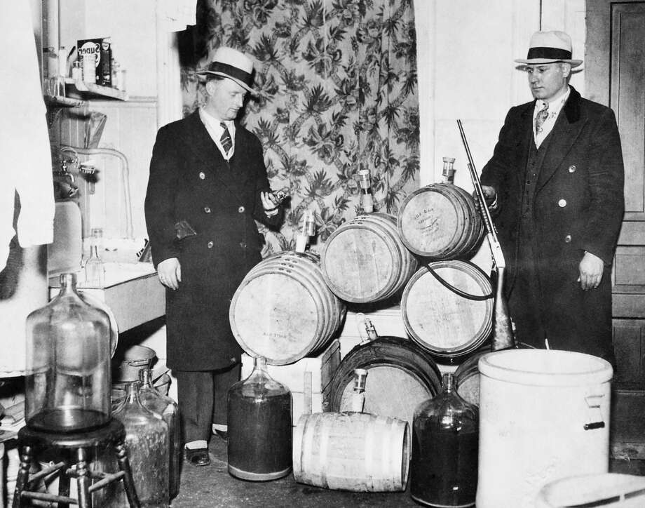 Police officers look over distilling equipment and guns confiscated during a prohibition raid, Chicago, ca.1920s. Photo: Chicago History Museum, Getty Images / Archive Photos