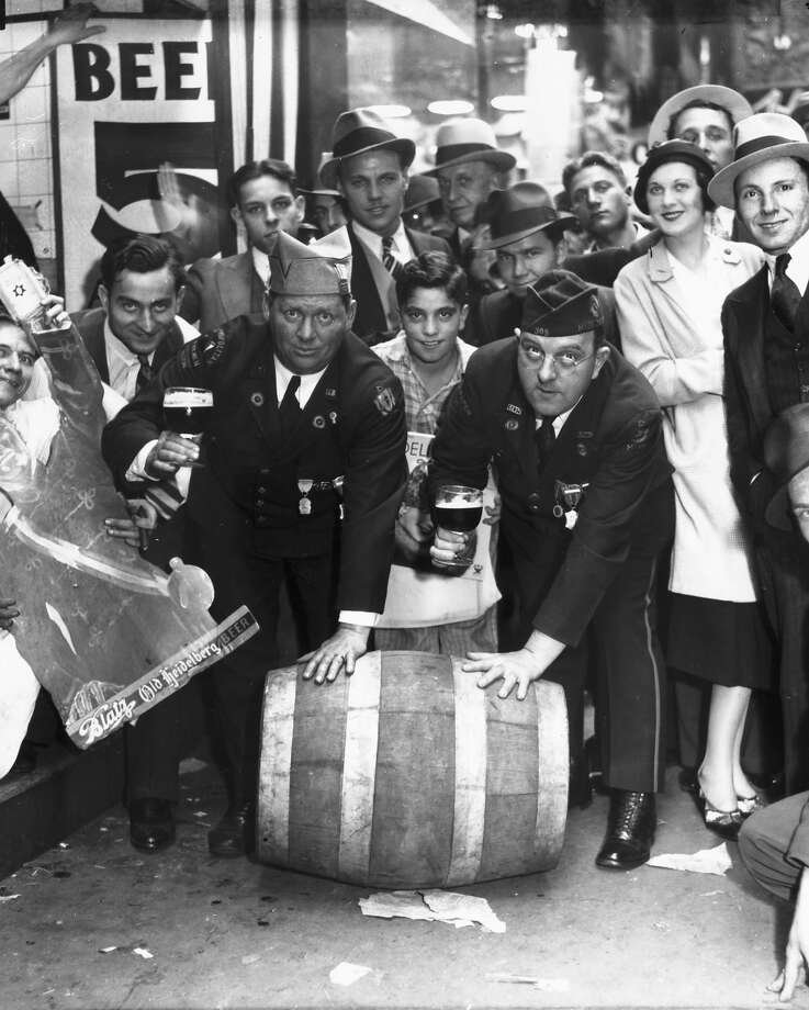 View of men and women celebrating the repeal of Prohibition by rolling down a barrel of alcohol and toasting the 18th Amendment's demise, Chicago, 1933. Two men in front are wearing Legionnaires' uniforms. Photo: Chicago History Museum, Getty Images / Property of Chicago Historical Society.  Not to be reproduced or used without written permission from CHS Rights & Reproductions Dept.
