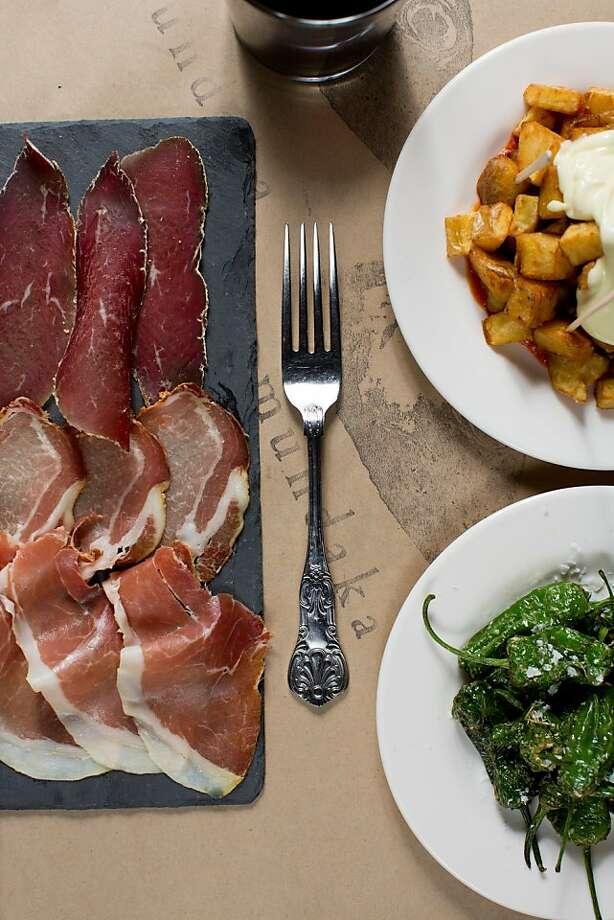 At Mundaka, the small plates, above, might include (clockwise from left) charcuterie, potatoes bravas and padron peppers. . Photo: Jason Henry, Special To The Chronicle