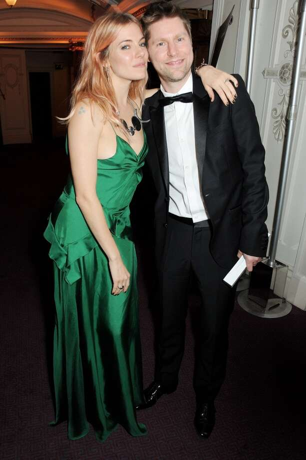 Sienna Miller (L) and Christopher Bailey, winner of Brand of the Year for Burberry, pose at the British Fashion Awards 2013 at London Coliseum on December 2, 2013 in London, England.  (Photo by David M. Benett/Getty Images) Photo: David M. Benett, Getty Images