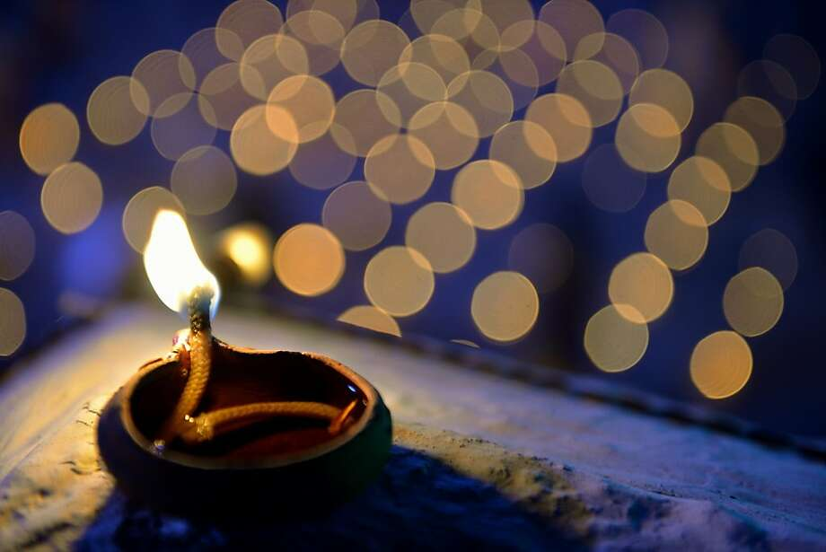 An oil lamp lightsa temple for the Hindu God Shiva during the Karthigai Deepam in   Bangalore. Karthigai Deepam is a festival of lights celebrated by Tamil Hindus on a full moon during November   and December. Photo: Manjunath Kiran, AFP/Getty Images