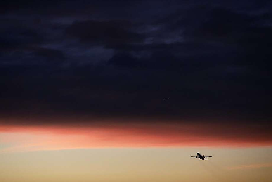 A plane takes off from the Los Angeles International Airport as clouds reflect the color of the sunset on Monday, Dec. 2, 2013, in Los Angeles. (AP Photo/Jae C. Hong) Photo: Jae C. Hong, Associated Press
