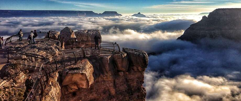 Canyon in the clouds:Visitors to Mather Point at Grand Canyon National Park look over a rare total cloud inversion. The phenomenon, caused by cold and warm air masses interacting, obscured much of the canyon beneath a sea of clouds. Photo: Erin Whittaker, Associated Press