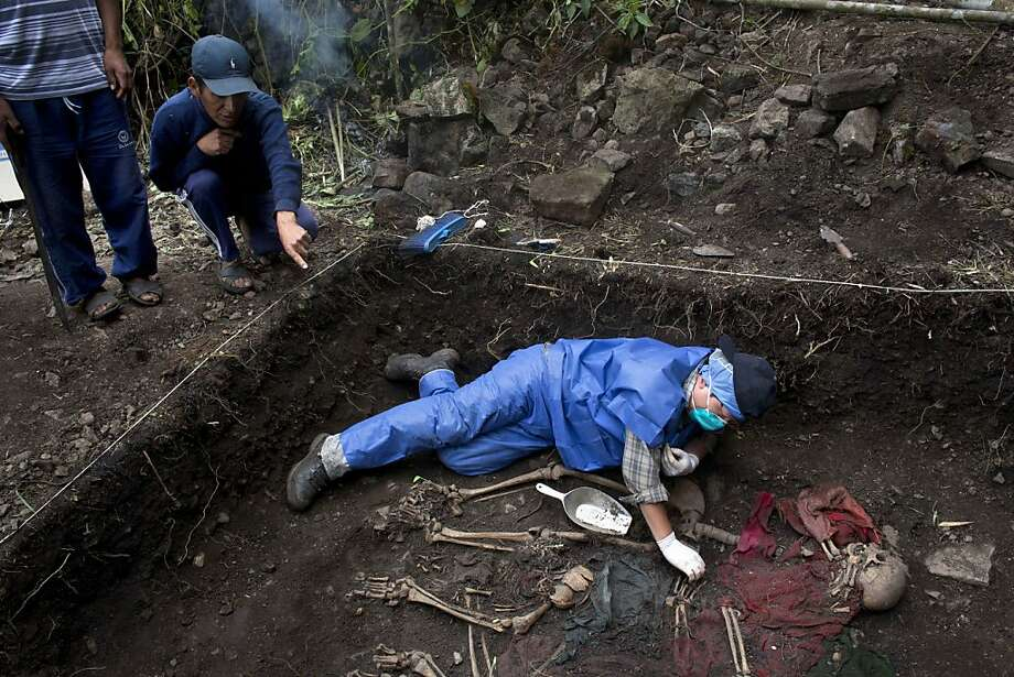 His mother's bones:Julio Orihuela, 37, points to the mass grave in the village of Huallhua where his mother and sister were buried   as forensic anthropologist Joel Tejada unearths their skeletal remains. The exhumation in the district of   Chungui, Peru, is bringing back traumatic memories for survivors of the atrocities of 1986-87, when soldiers and their   paramilitary allies dismembered and killed women and children left behind by fleeing Shining Path rebels. Photo: Rodrigo Abd, Associated Press