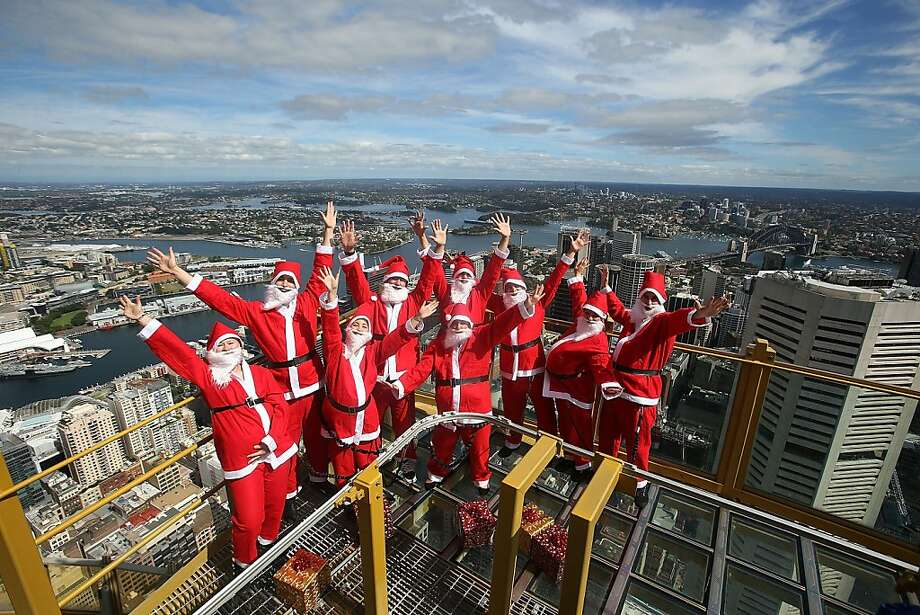 High up down under:It's beginning to look a lot like a Santa convention on the Skywalk of the Sydney Tower in Sydney. Photo: Mark Metcalfe, Getty Images