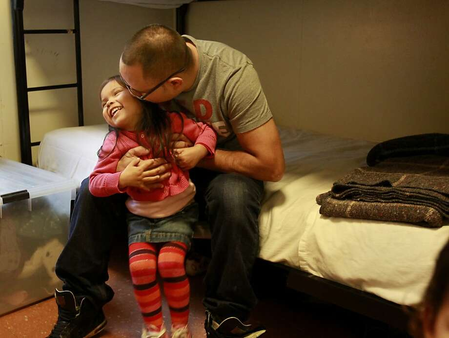 Christopher Ramirez gave his daughter Emily Grace a kiss in the room they live in at the Hamilton Family Residence Wednesday November 20, 2013 in San Francisco, Calif. The Ramirez family, after years of homelessness and living in shelters, won a lottery and will soon move into a brand new apartment on Market Street. Photo: Brant Ward, The Chronicle