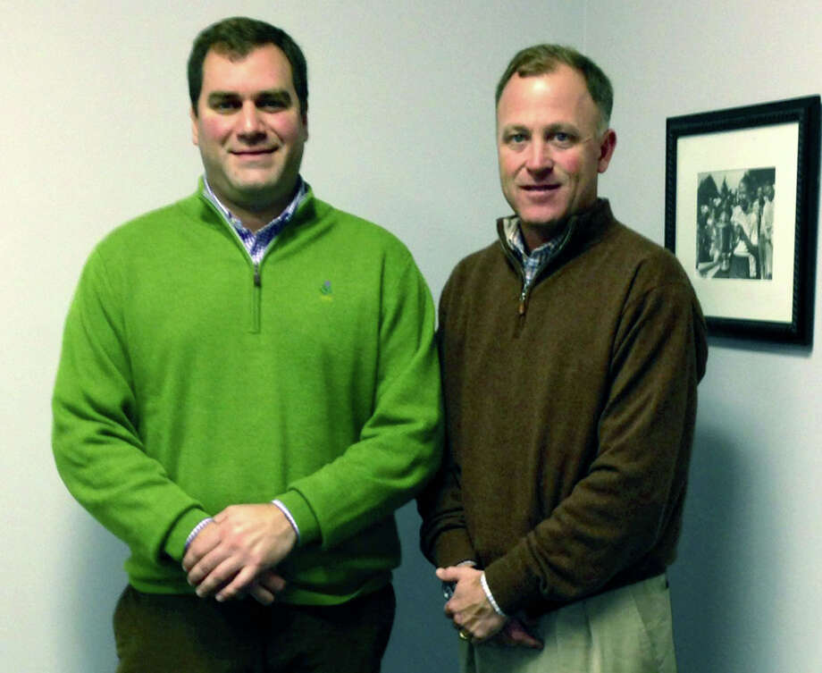 Paul Ramee, right, golf director at Bull's Bridge Golf Club in South Kent, and Bull's Bridge assistant pro Chris Stahlnecker welcome patrons to Golf on the Green along Main Street in New Milford. November 2013  Courtesy of Golf on the Green Photo: Contributed Photo / The News-Times Contributed