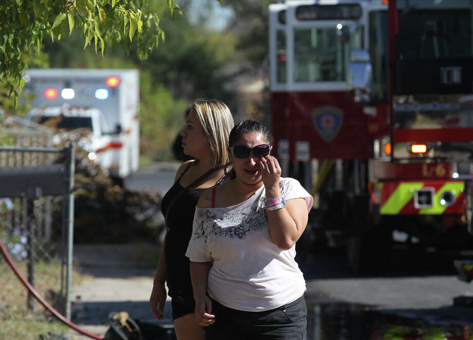 Emily Flores (front, wearing white shirt) wipes tears from her eye Tuesday December 3, 2013 after seeing her mother's burned home on the 500 block of West Hermosa. San Antonio fire Captain Michael Moore said one occupant got out of the house safely and the house is pretty much a total loss. Emily Flores identified her mother as Elva Flores. Moore said arson is investigating the cause of the fire. Photo: JOHN DAVENPORT, SAN ANTONIO EXPRESS-NEWS / ©San Antonio Express-News/Photo may be sold to the public