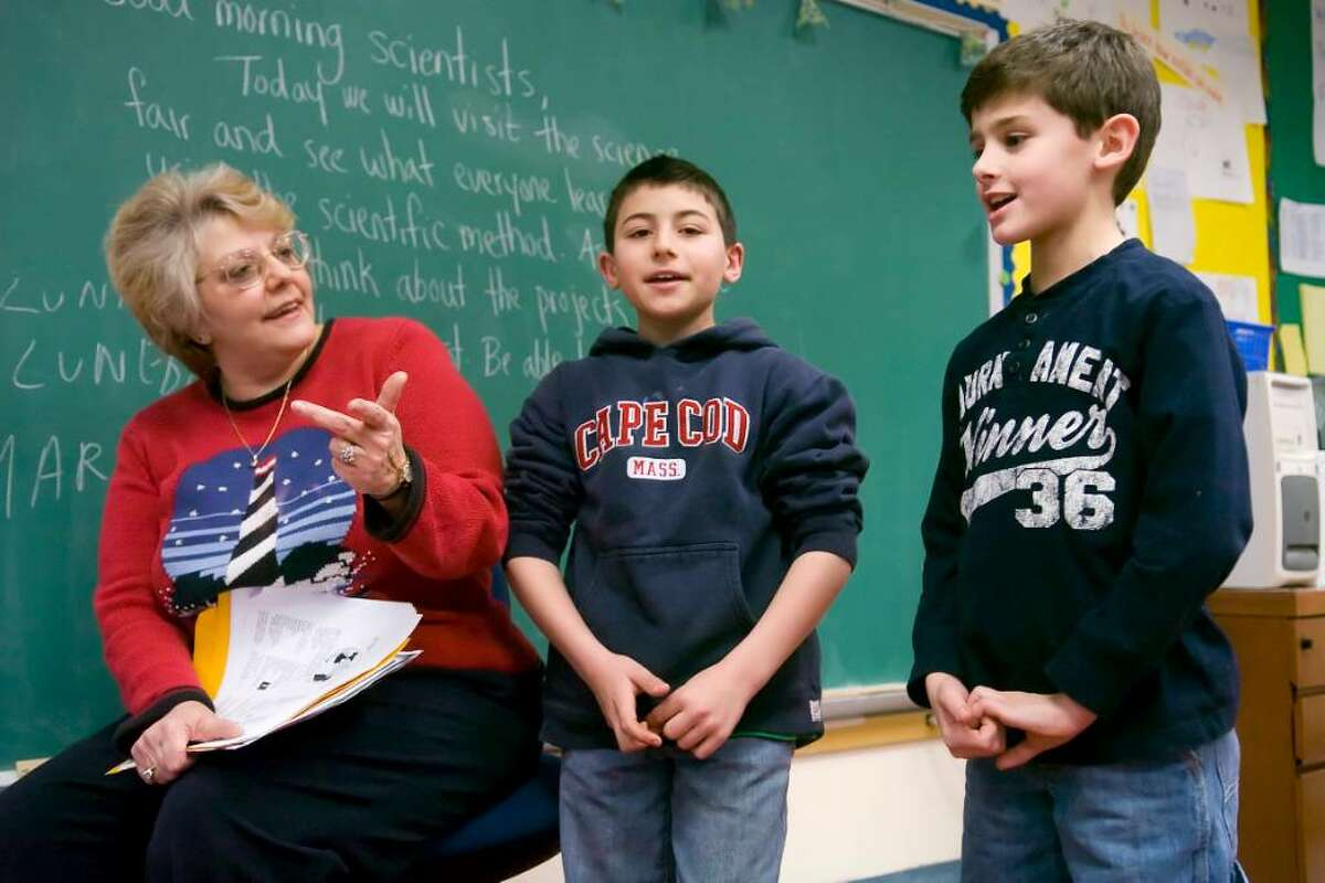 Teacher Flavia Lasalandra, sings a song in Italian with students Anthony Rizzi, center, 10, and Anthony Tedesco, right, 9,with during the after-school language program at Newfield Elementary School in Stamford, Conn. on Wednesday, Jan. 27, 2010