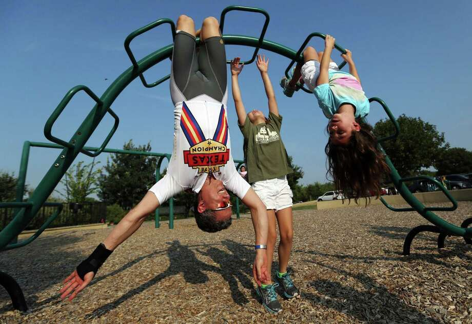 Dr. Ken Adams gets a good workout playing with his daughters Isabelle, center, and Katherine at White Rock Lake's playground in Dallas. Photo: Ricky Moon, MBR / Dallas Morning News