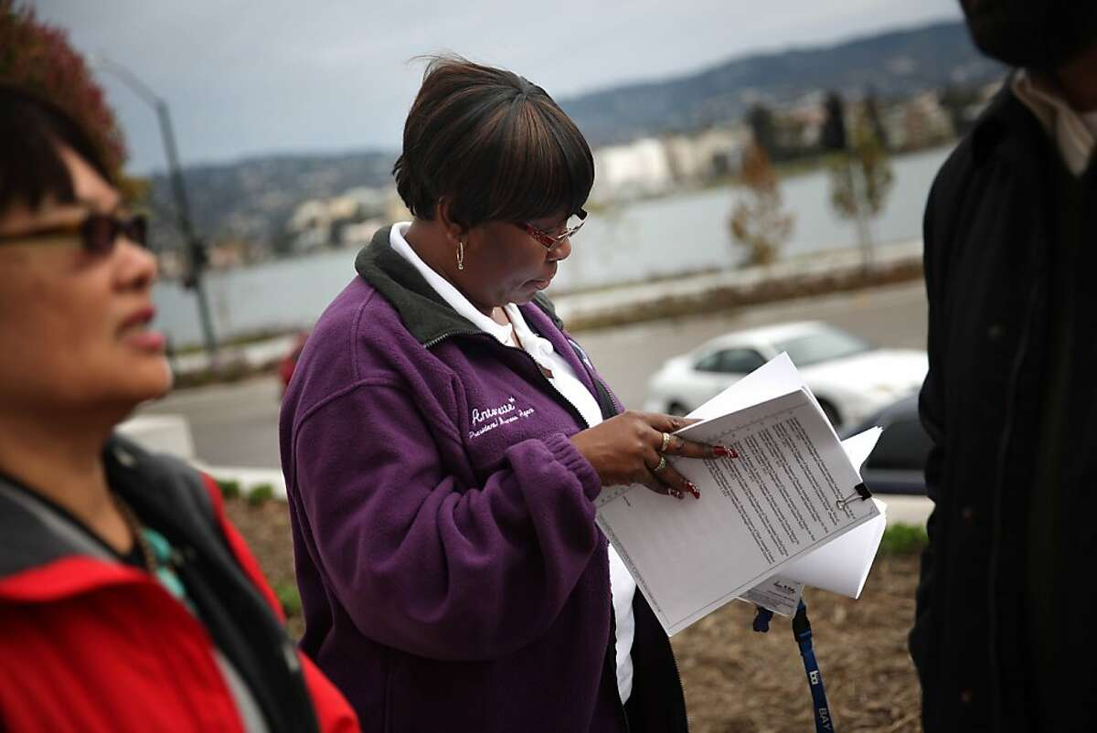 Antonette Bryant, president ATU 1555, looks over a copy of the lawsuit before a press conference announcing the filing of a lawsuit against the BART board of directors over a contract dispute while standing outside the Rene C. Davidson Courthouse on Tuesday, December 3, 2013 in Oakland, Calif.