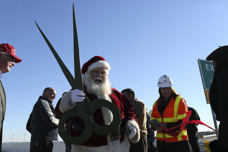 Santa Claus, also known as Eldon Hansen, holds the ribbon-cutting scissors Nov. 27 at the opening of the new Forum Parkway ramp at Interstate 35 and Loop 1604. Photo: Lisa Krantz / San Antonio Express-News