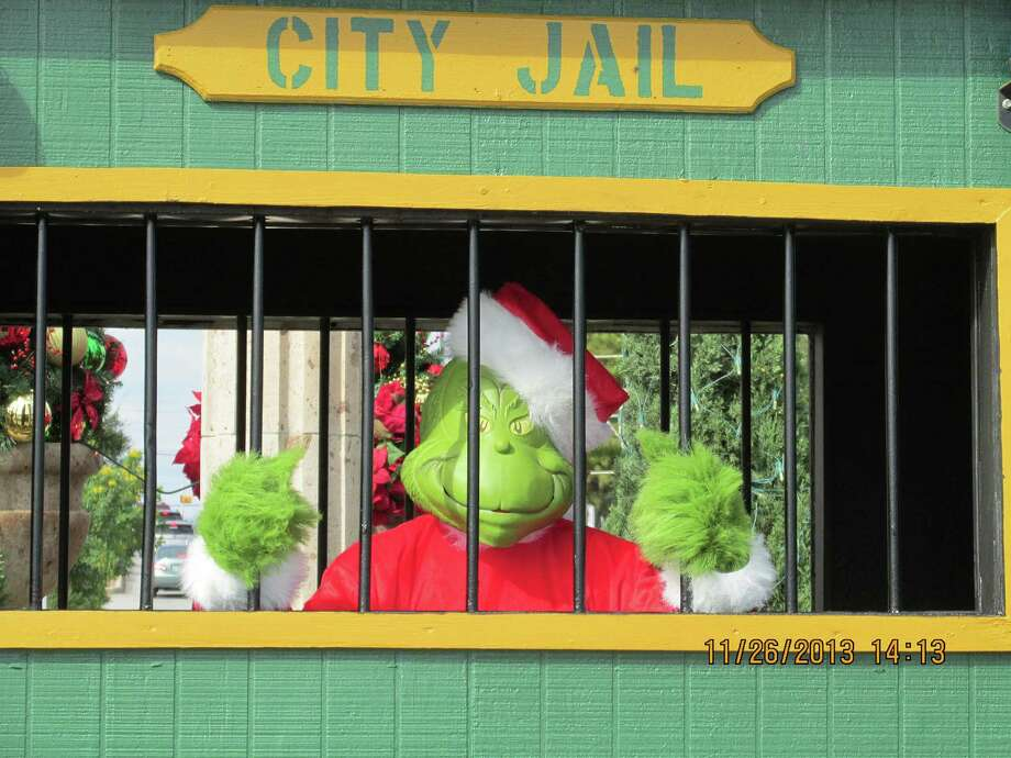"""The Grinch is behind bars, locked up during the launch of """"Operation Grinch,"""" a joint law enforcement effort to protect The Forum holiday shoppers from criminals. Click through to see which San Antonio area stores and shopping centers will be open on Christmas Eve. Photo: Courtesy Photo"""