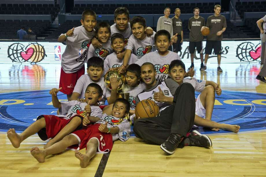 Patty Mills of San Antonio Spurs poses for a picture with Triquis native boys at the Arena Ciudad de Mexico, in Mexico City, on December 3, 2013. Timberwolves will face San Antonio Spurs next December 4 in a NBA game. The team of the Triquis natives --from the southern state of Oaxaca-- took first place at the International Festival of Mini-Basketball in Argentina last October.  AFP PHOTO/RONALDO SCHEMIDTRONALDO SCHEMIDT/AFP/Getty Images Photo: RONALDO SCHEMIDT, AFP/Getty Images / RONALDO SCHEMIDT