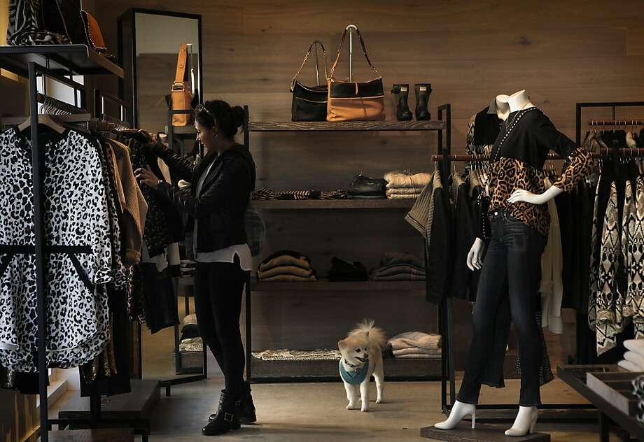 Chaliz Afshar, fashion blogger for glamourhouse.com., browses through merchandise at Intermix with her dog Mooshi in the Marin Country Mart in Larkspur. Photo: Liz Hafalia, Chronicle