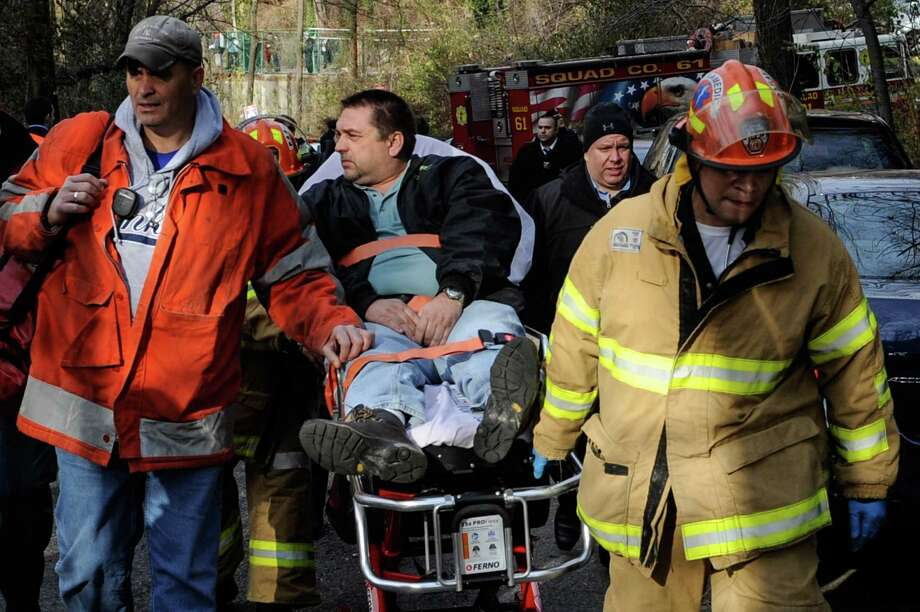 In this photo taken on Sunday, Dec. 1, 2013, Metro North Railroad engineer William Rockefeller is wheeled on a stretcher away from the area where the commuter train he was operating derailed in the Bronx borough of New York. The National Transportation Safety Board reported Monday that the train Rockefeller was driving was going 82 mph around a 30-mph curve when it derailed killing four people and injuring more than 60. (AP Photo/Robert Stolarik) Photo: Robert Stolarik, FRE / AP