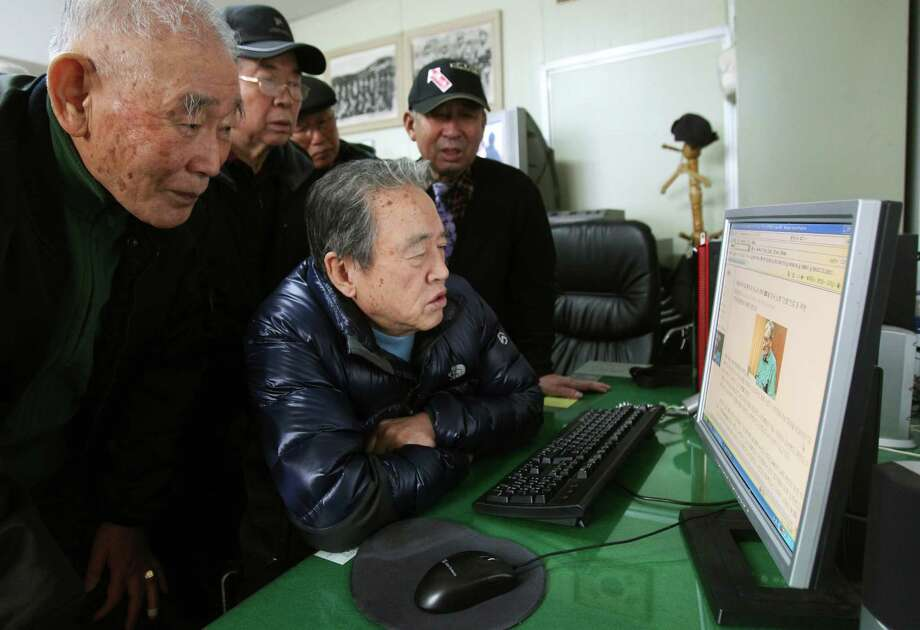Park Young, center, and others who were South Korean guerrillas during the Korean War, view a website reporting on Merrill Newman, their former supervisor. Photo: Ahn Young-joon, STF / AP