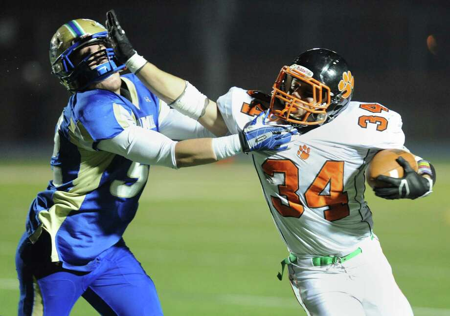 Ridgefield running back Will Bonaparte (34) stiff arms Newtown defender Nick Samuelson (52) in the CIAC Class LL state quarterfinal football game between Ridgefield and Newtown at Newtown High School in Newtown, Conn. on Tuesday, Dec. 3, 2013. Photo: Tyler Sizemore / The News-Times